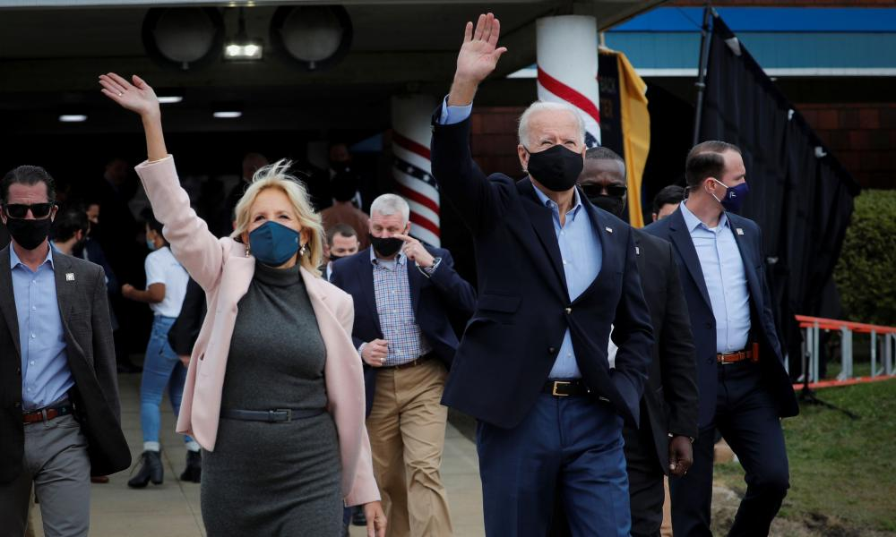 Former Vice President Joe Biden and his wife Jill wave to supporters as they walk to an Amtrak train to begin a campaign train tour in Cleveland, Ohio.