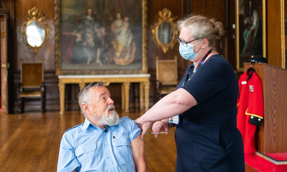 Chelsea pensioner John Byrne receives a Covid-19 booster jab from deputy chief nurse Vanessa Sloane at the Royal hospital Chelsea in London
