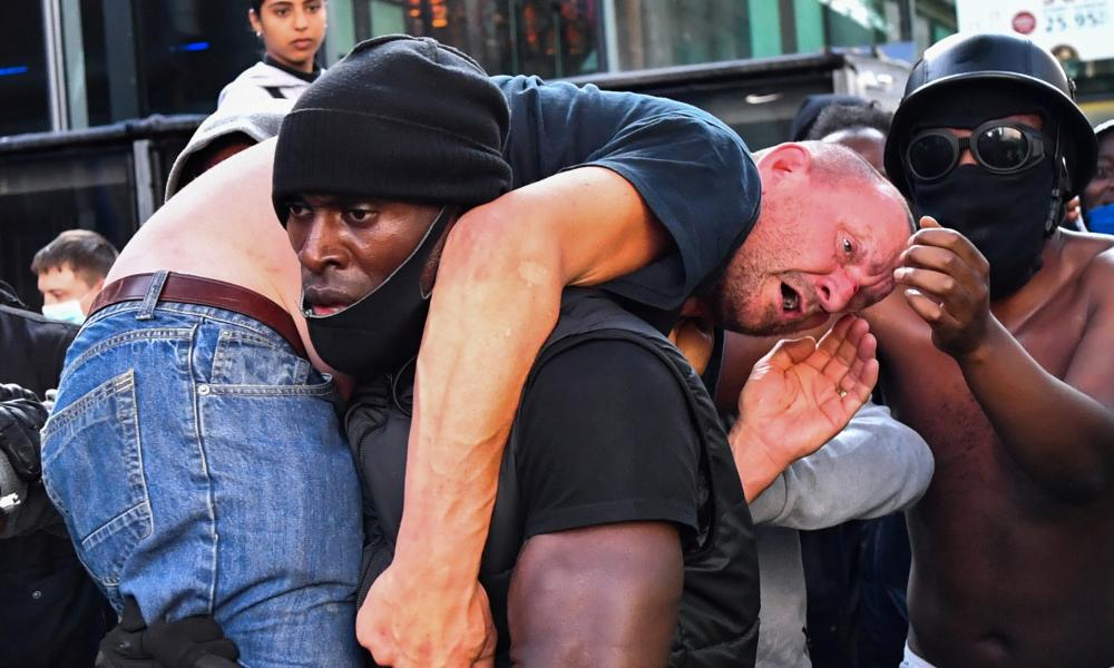 A protester carries an injured counter-protester to safety, near the Waterloo station during a Black Lives Matter protest following the death of George Floyd in Minneapolis police custody, in London, Britain, June 13, 2020.