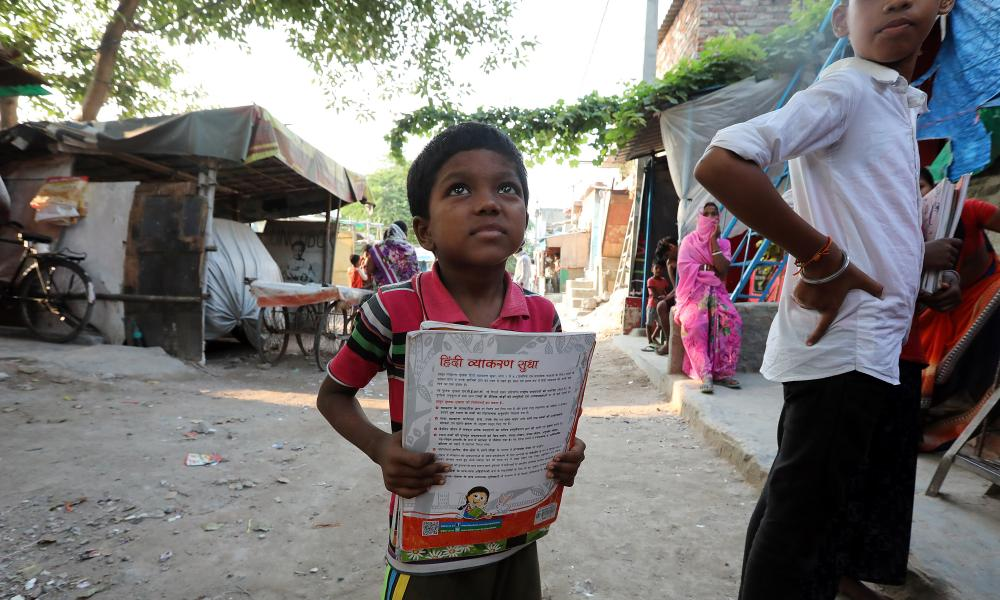 A boy holds a textbook outside his home at the Shahdara drain slum area on the outskirts of New Delhi. The Covid-19 pandemic has disrupted the education of millions of children and increased their vulnerability to exploitation.