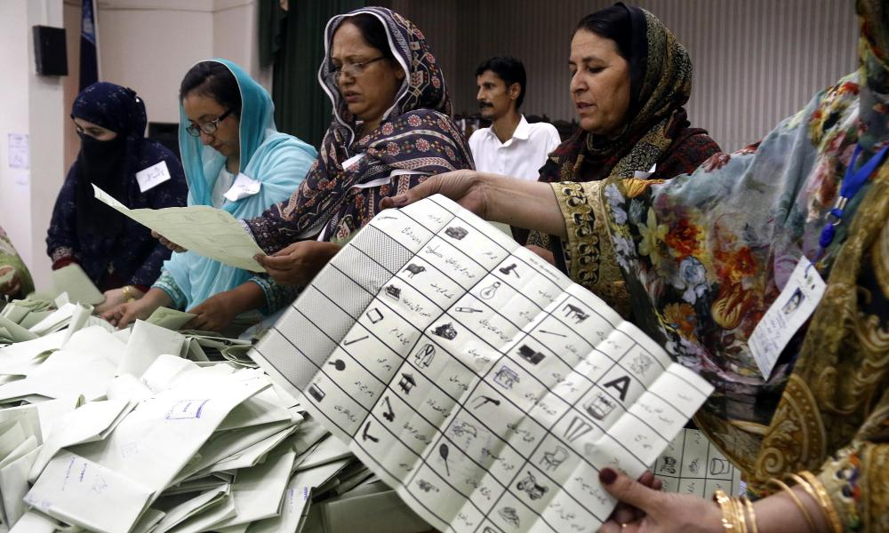 Polling officers count ballots at a polling station as the general elections concluded, in Islamabad, Pakistan