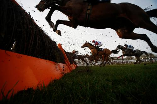 Horses and their jockeys clear a hurdle at Chepstow racecourse in south Wales. Tuesday's meet included the Welsh Grand National, one of the biggest races of the UK jumps season
