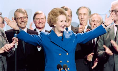 THATCHER-PARTY<br>British Prime Minister Margaret Thatcher acknowledges applauds on Ocotber 13, 1989 at the end of the Conservative Party conference in Blackpool. At left Foreign Secretary John Major and at right Home Secretary John Hurt.        (Photo credit should read JOHNNY EGGITT/AFP/Getty Images)