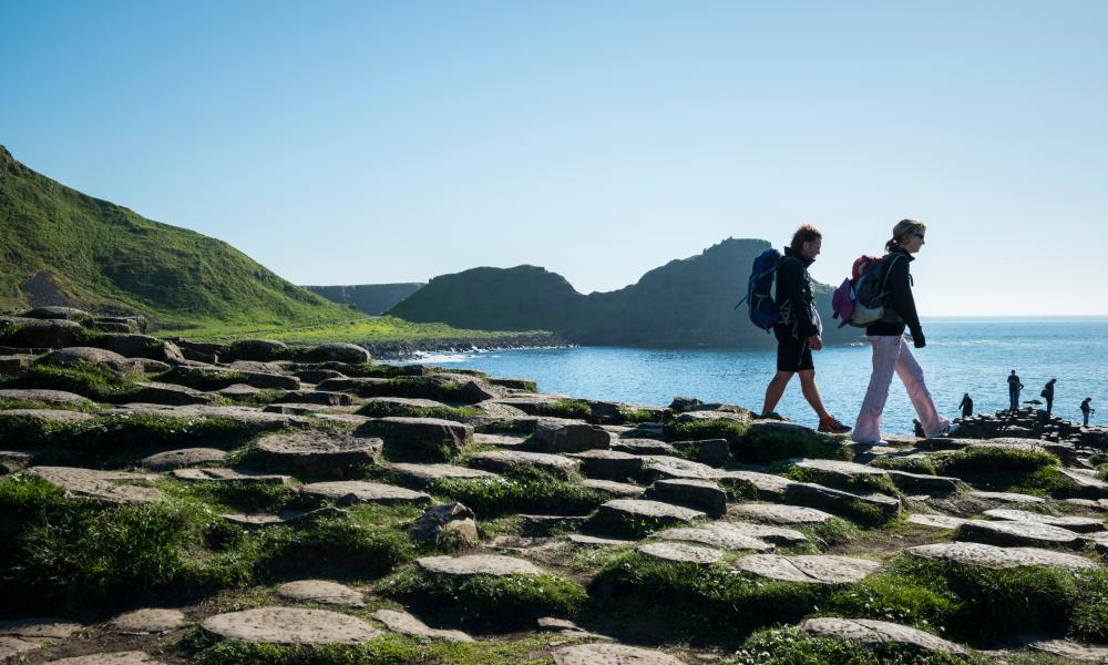 Giant's Causeway in Northern IrelandBushmills, Northern Ireland, U.K. - June 7, 2013: Visitors wearing backpacks walk on the geologically unique coastline