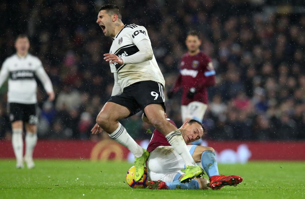 Mark Noble launches himself into a chalenge on Fulham's Aleksandar Mitrovic.