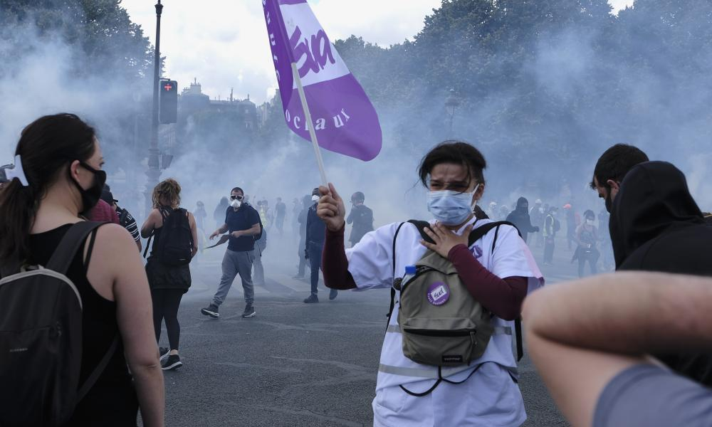 A woman is overcome by teargas as hospital staff protest in Paris to denounce the state of the French public health system.