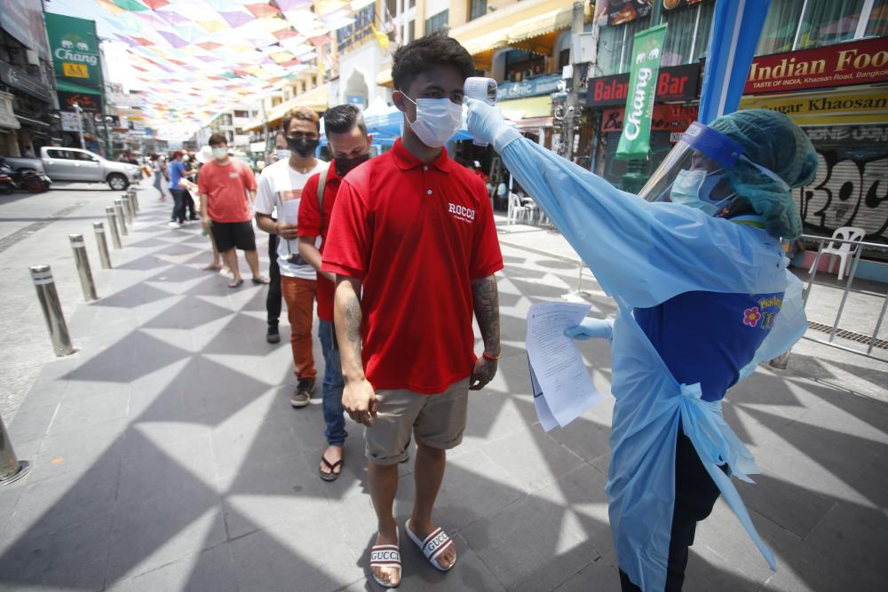 A health worker checks the temperature of a man falling in line for a Covid-19 swab test in Khaosan Road in Bangkok, Thailand.