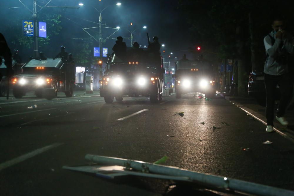 Riot police advance on protesters gathered in front of the Serbian parliament.