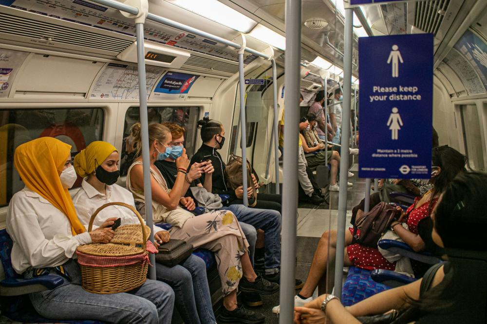 People travelling on the London Underground on 1 August, 2020 are wearing facemasks, which has become mandatory on public transport where social distancing is not possible. Passenger numbers are now rising as the government has eased lockdown restrictions and encouraged people to go to work.
