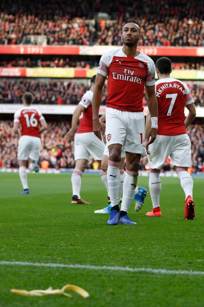 December 2: A banana thrown from Tottenham section lies on the pitch as Arsenal's Gabonese striker Pierre-Emerick Aubameyang looks on.