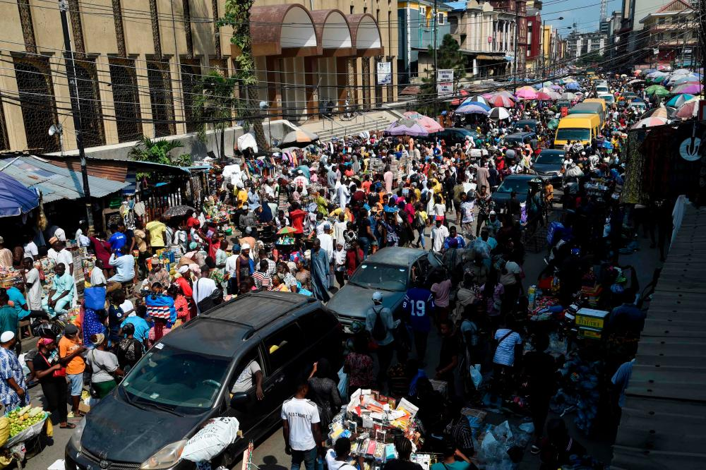People walk along cars on 29 July, 2020 on Nnamdi Azikiwe Street in Lagos, Nigeria's commercial hub and epicentre of the virus in the country.