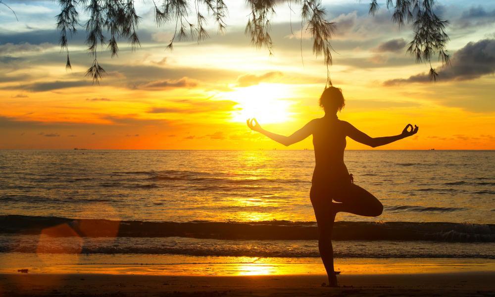 Young woman practising yoga at sunset