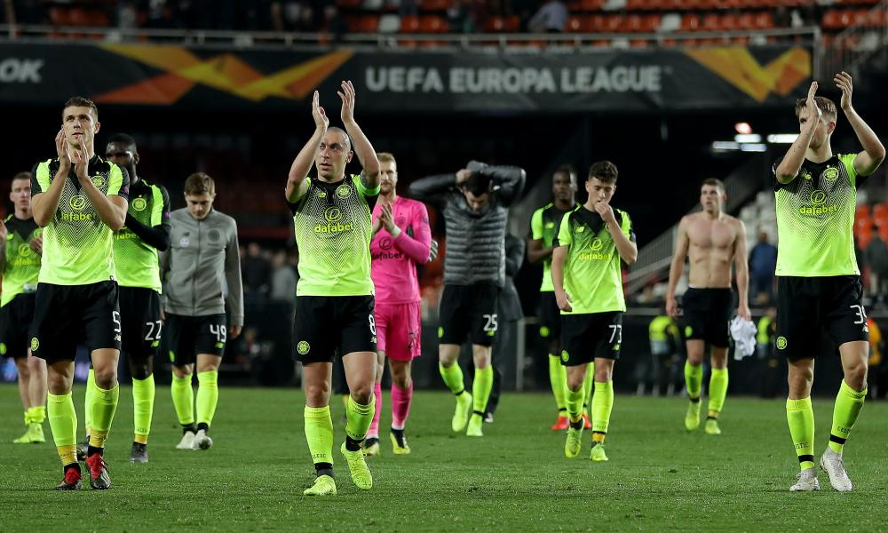Celtic players applaud their fans after the final whistle.