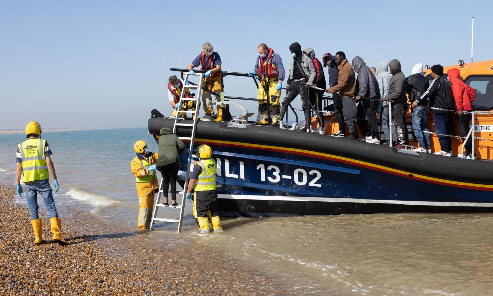 A group of people are brought ashore from a lifeboat at Dungeness in Kent. More than 800 migrants crossed the Channel on Monday.