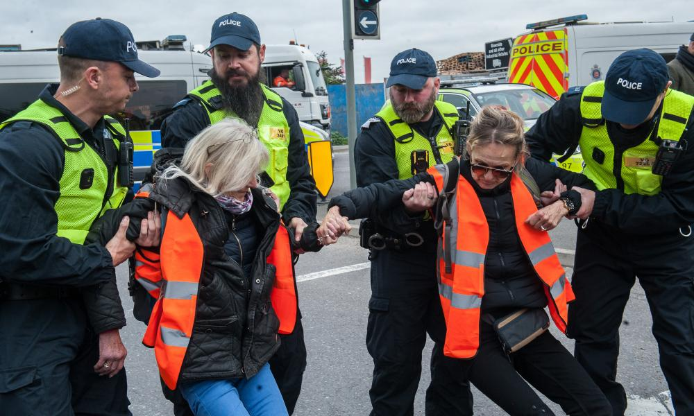 Police removing protesters as activists from Insulate Britain block a junction near the Dartford Crossing in Thurrock, Essex