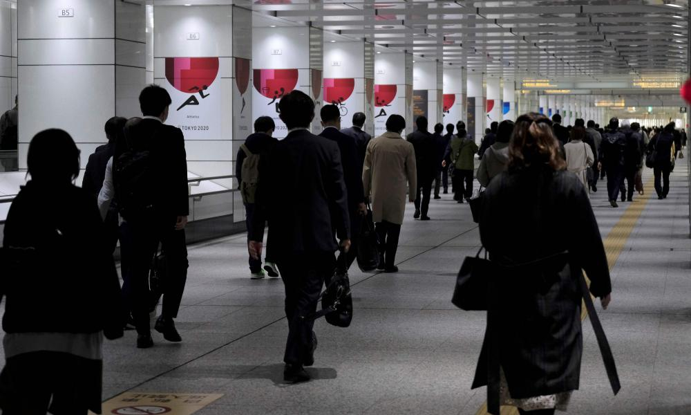 Commuters head to work through an underpass connecting from Shinjuku railway station in Tokyo on 9 April 2020.