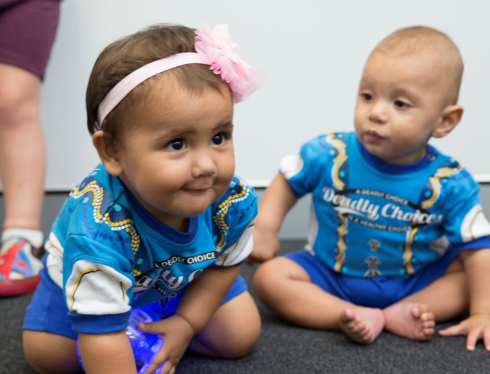 Aboriginal and Torres Strait Islander children wearing Deadly Choices onesies after completing health milestones – health checks and immunisations at an IUIH clinic.