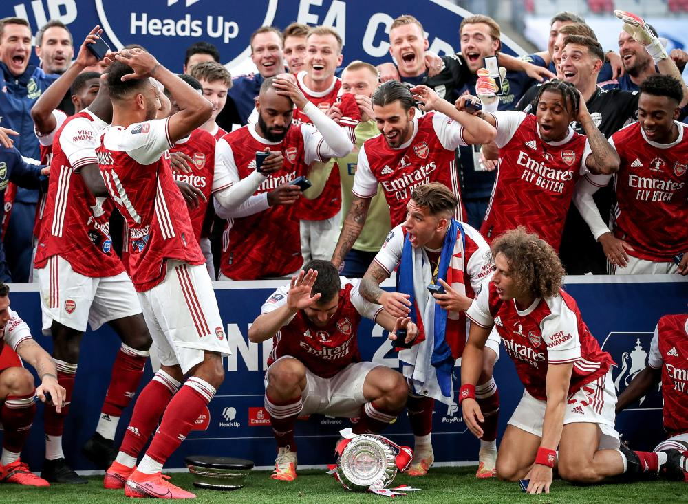 Arsenal's Pierre-Emerick Aubameyang (centre) drops the FA Cup troph.