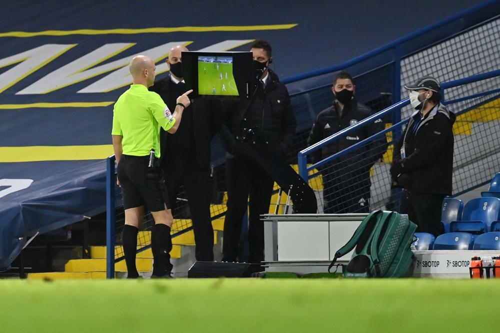 Referee Anthony Taylor checks the VAR monitor