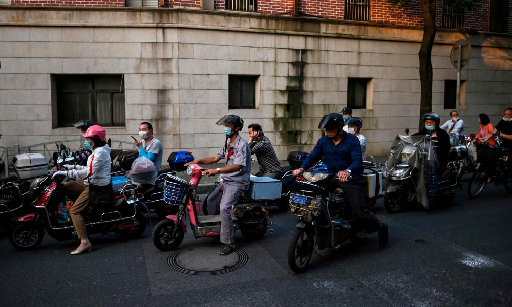 People wearing face masks wait for the green light while riding scooters on a street in Shanghai.