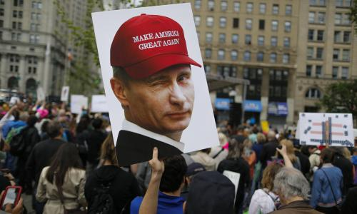 A demonstrator holds up a sign of Vladimir Putin during an anti-Trump rally on 3 June 2017 in New York City.