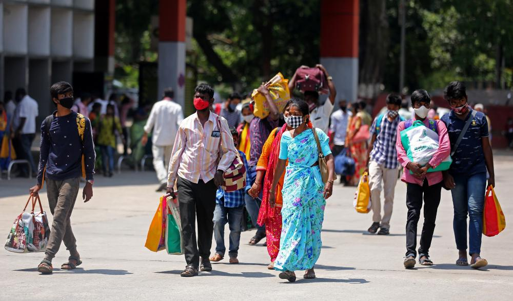 Indian migrant workers and people walk down to go back to their home town at the city railway station in Bangalore, India, on 26 April 2021.