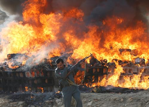 An Afghan officer turns away from the heat as about 98 tonnes of drugs seized by counter-narcotics police and security forces, including opium and heroin, are burned on the outskirts of Kabul, Afghanistan