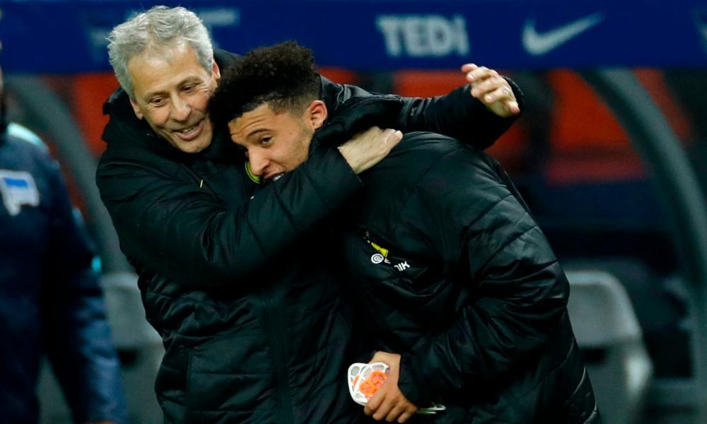 Dortmund's head coach Lucien Favre hugs Jadon Sancho after the final whistle.