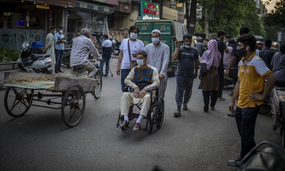 Afghan refugee pushes man in wheelchair