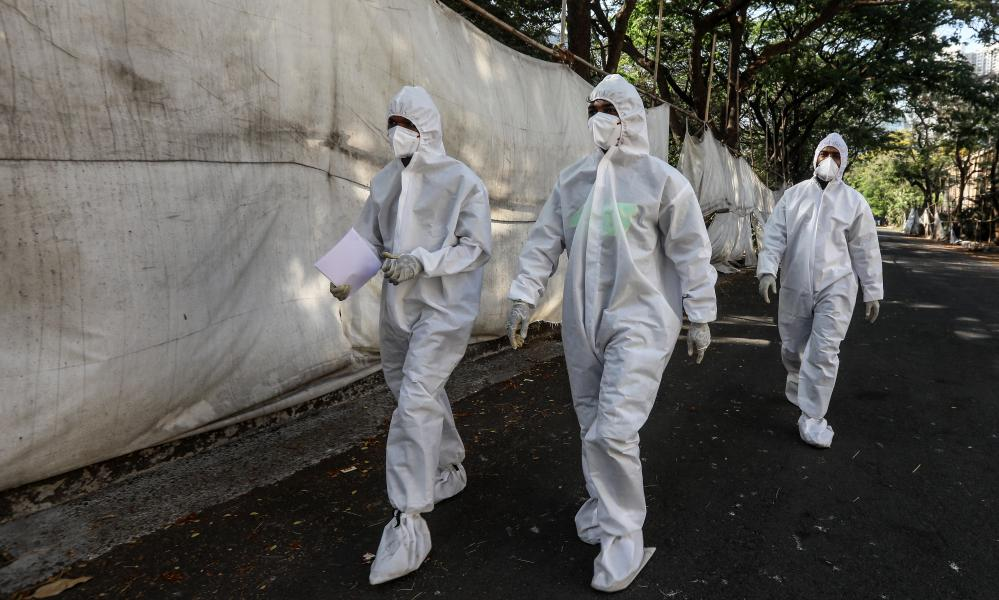 Health workers wearing personal protective equipment walk past a quarantine centre in Mumbai, India, 5 April 2021.