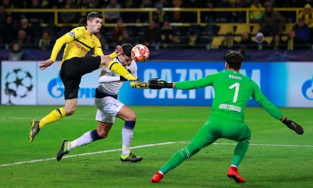 Borussia Dortmund's Christian Pulisic ensures Tottenham's Erik Lamela can't get his purchase on his header.