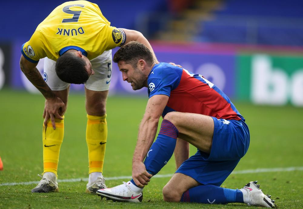 Lewis Dunk checks on Crystal Palace's Gary Cahill after the lunge that led to a red card for Brighton's captain