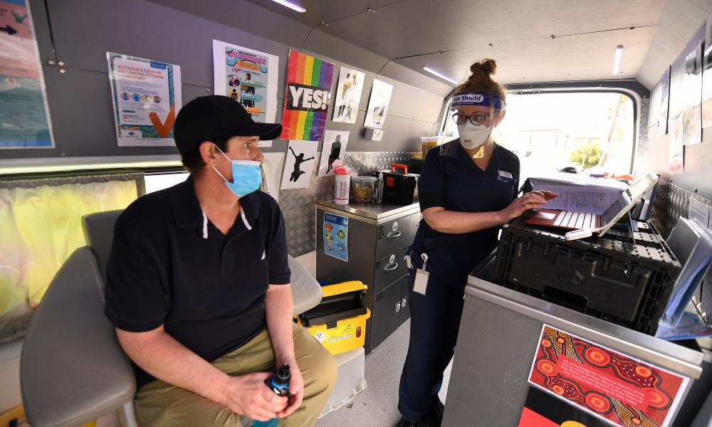 A healthcare workers speaks with a patient prior to administering a Covid-19 vaccination at a St Vincent's mobile immunisation location in Melbourne on 10 September.