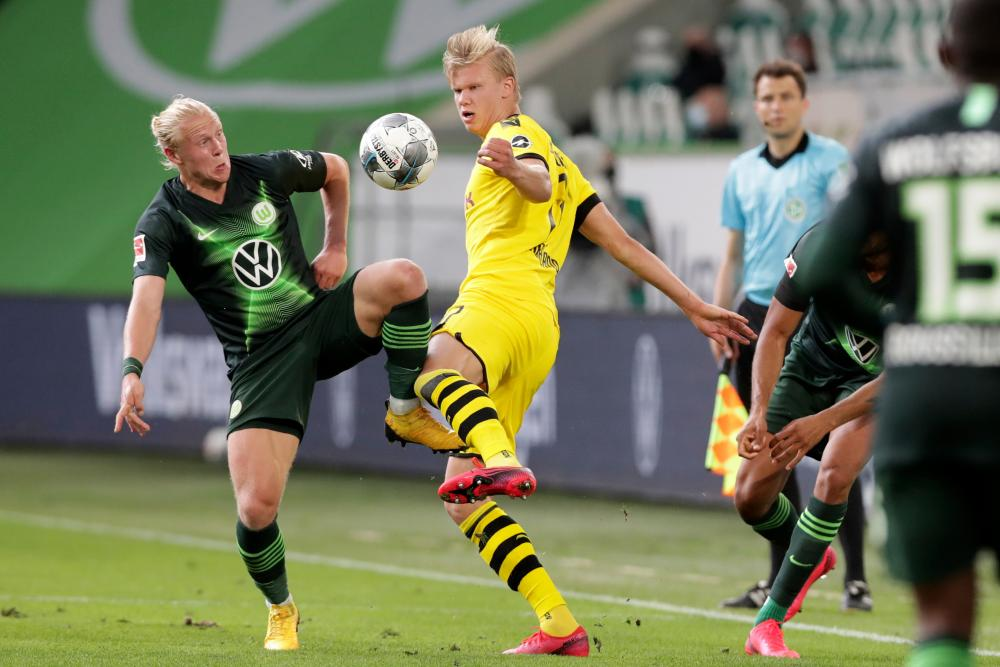 Wolfsburg's Xaver Schlager (left) vies for the ball with Dortmund's Erling Haaland.