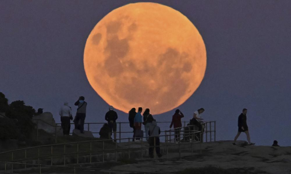 People watch as the 'super flower blood moon' rises over Bondi Beach in Sydney on 26 May, 2021. Guardian Australia's picture editor explains how to photograph the moon, whether you're using a phone or DSLR camera, and the best settings to use.