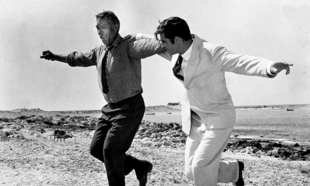 Film still of two men in suits with their arms round each others shoulders dancing
