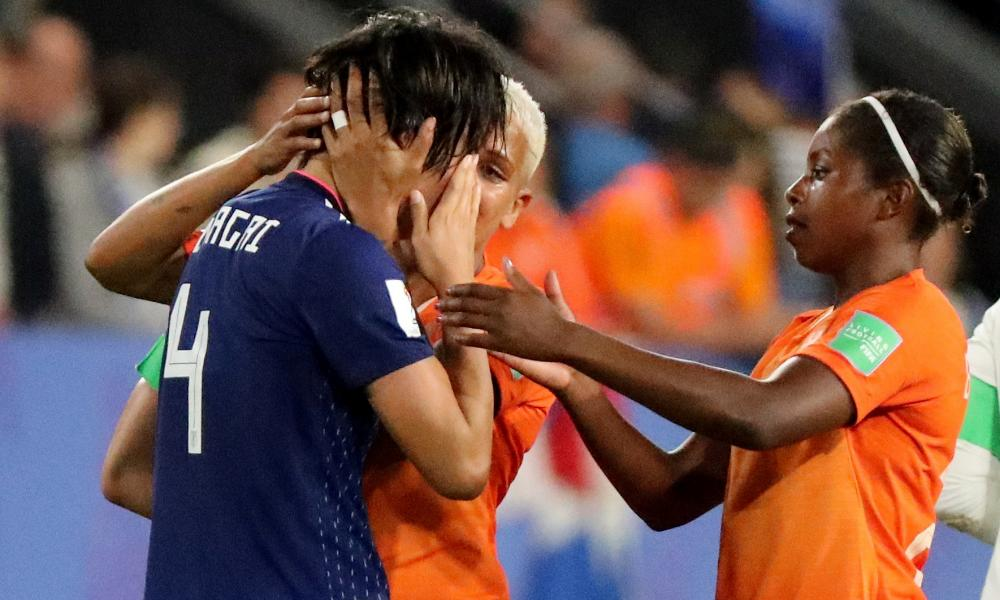 Japan's Saki Kumagai is consoled by Netherlands' Shanice van de Sanden and Lineth Beerensteyn.