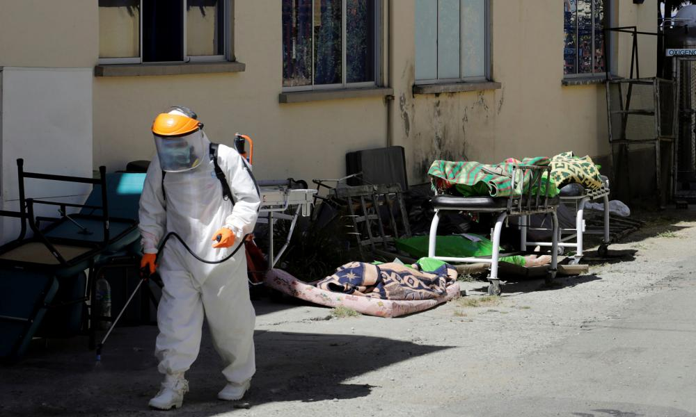 A health worker sprays disinfectant near the bodies that officers of the Special Force Against Crime (FELCC) transported to the 'Hospital de Clinicas' in La Paz, Bolivia.