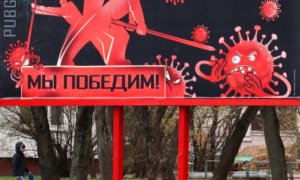 "A young man walks a dog by a billboard reading ""We will win"" in Minsk, Belarus."