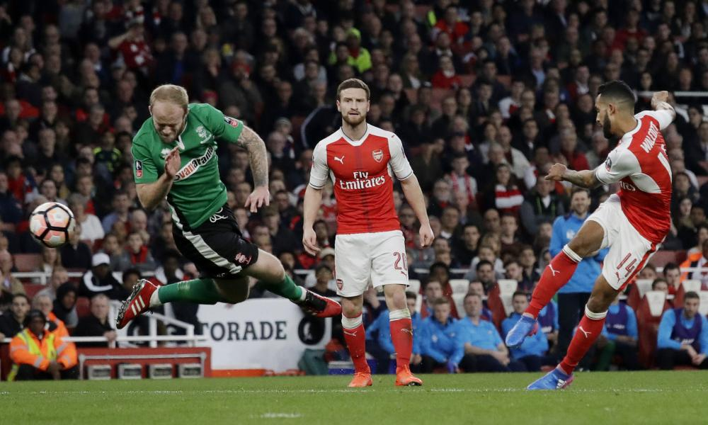 Arsenal's Theo Walcott, right, takes a shot at goal as Lincoln City's Bradley Wood, left, attempts to block the shot.