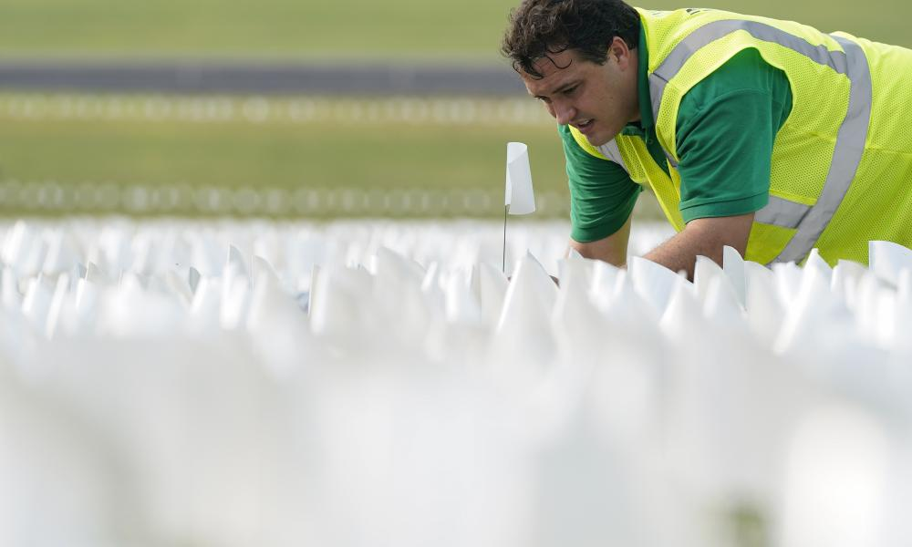 A worker plants white flags on the National Mall in Washington as part of artist Suzanne Brennan Firstenberg's temporary art installation, In America: Remember to commemorate those who have died from coronavirus.
