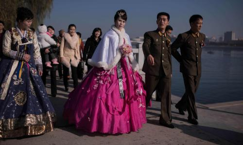 A bride and groom walk with relatives and friends as they prepare to pose for their wedding photos by the Taedong river in Pyongyang