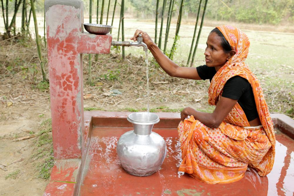 Bina Patrou, a tea picker at the Gulni tea estate, collects water from a pump installed by WaterAid and partners.