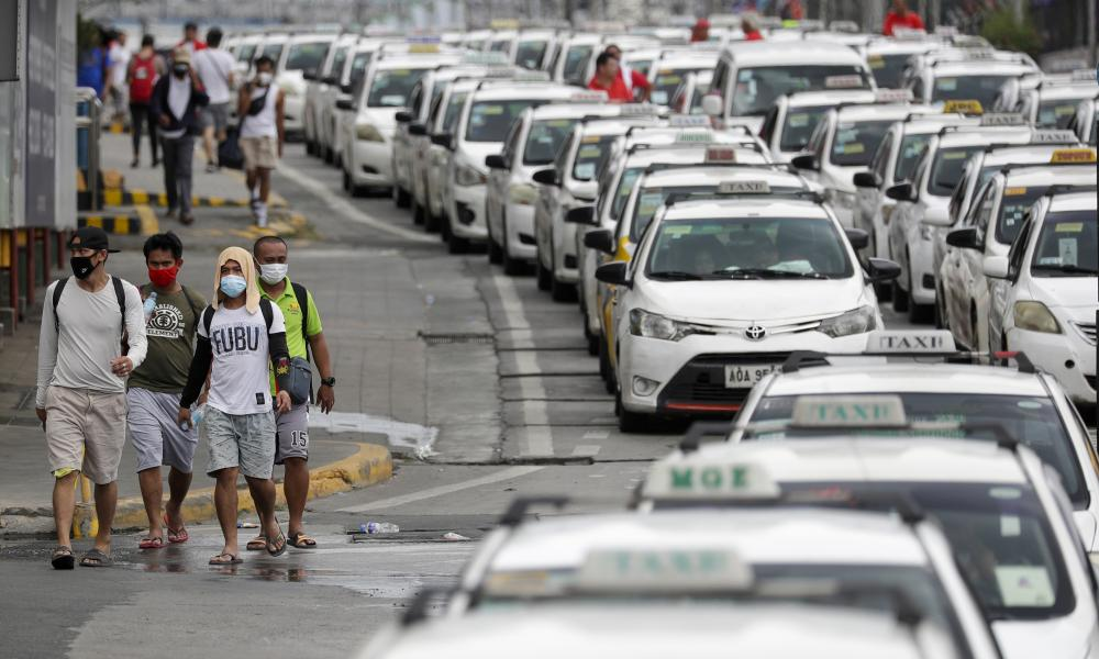 """Rows of taxis that were instructed by police to stop operations while the government implements the """"enhanced community quarantine"""" as a precautionary measure against the spread of the new coronavirus in Metro Manila, Philippines, early Tuesday, March 17, 2020."""