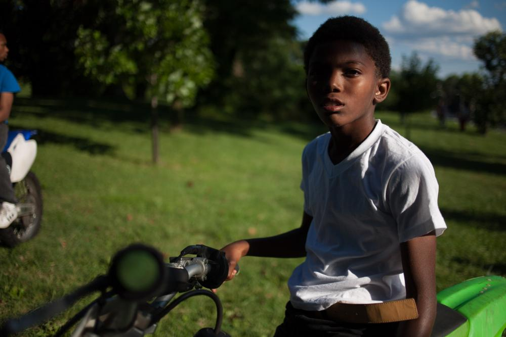 A young Baltimore rider at a wheel deal. Dirt bike riders are heroes to many kids in the city