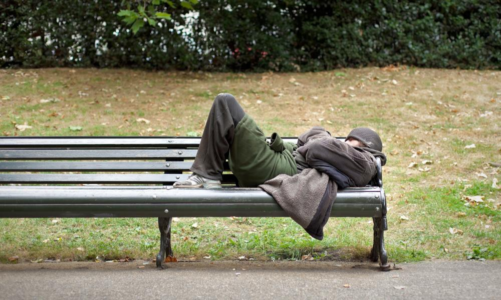 A homeless man sleeping on a bench in central London