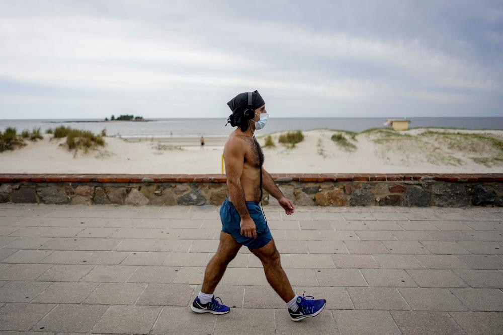 A man wearsg a mask as a precaution as he walks by the beach in Montevideo, Uruguay