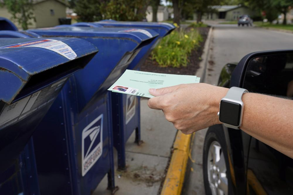 A person drops applications for mail-in-ballots into a mail box in Omaha, Nebraska.