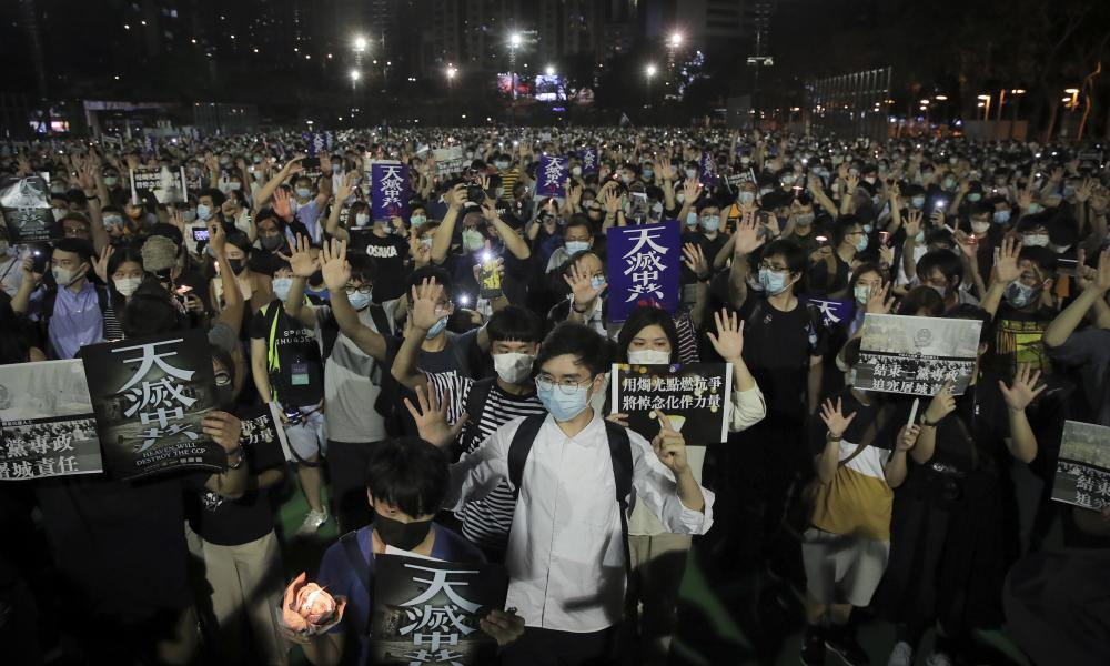 """Participants gesture with five fingers, signifying the """"Five demands - not one less"""", during a vigil for the victims of the 1989 Tiananmen Square massacre at Victoria Park in Hong Kong on Thursday."""