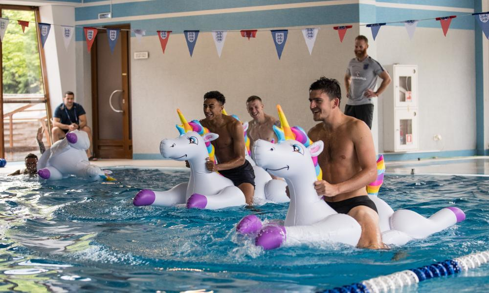Members of the England football team play with inflatable unicorns in the pool